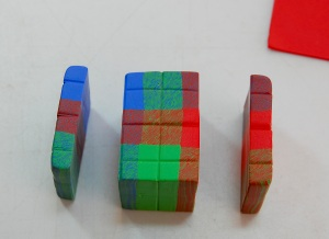 Note the position of the colors.  I slice through the squares on sides of the cane, using the scored lines as a guide, and keeping my cut as straight as possible.